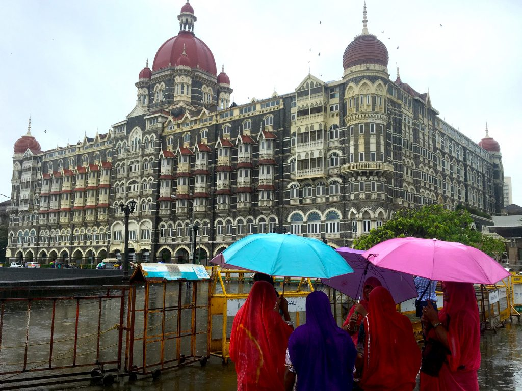 Women in colorful sarees with colorful umbrellas looking at the Taj Mahal Hotel across from the Gateway of India