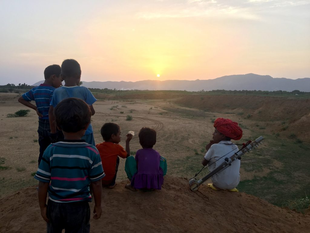 Kids watching the sunset over the sand dunes in Pushkar